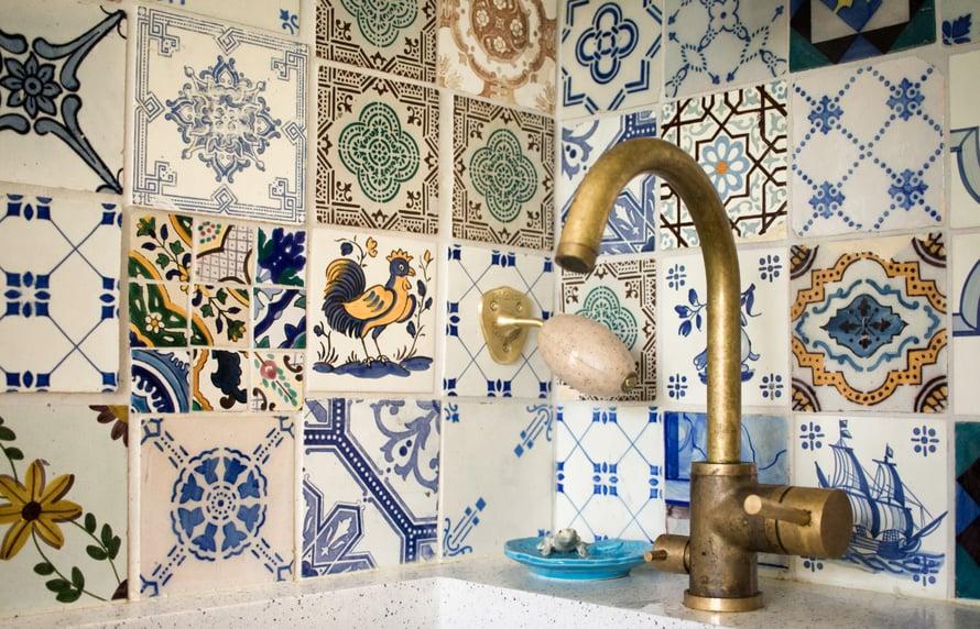Keittiön seinälaatat löysimme Lissabonin varkaiden markkinoilta, ne on pelastettu purkutaloista ja niiden putsaamiseen meni meiltä yksi päivä. Yksi laatoista puuttui laskuvirheen vuoksi ja ratkaisimme asian laittamalla puuttuvan tilalle paloja Tunisian-lomalta tuomistani kaakeleista. Homma ei olisi onnistunut ilman seikkailunhaluista laatoittajaa!