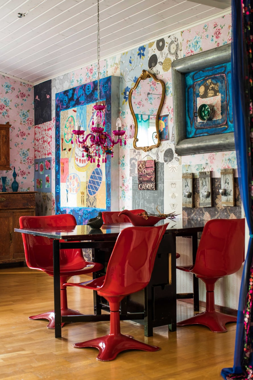 Olohuoneen seinä on koristeltu tapetinpaloilla ja tauluilla. Punaiset muovituolit tuovat tuulahduksen 1970-luvulta.