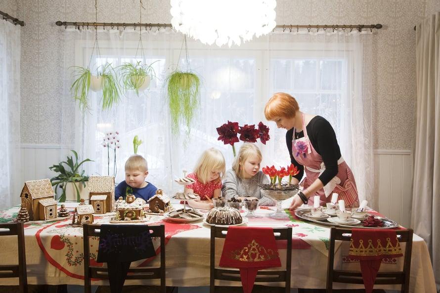 Suuren pöydän ääreen koko perhe – Eero, Siiri, Veera ja Katja – kokoontuvat piirtämään ja kokoamaan piparitaloja.