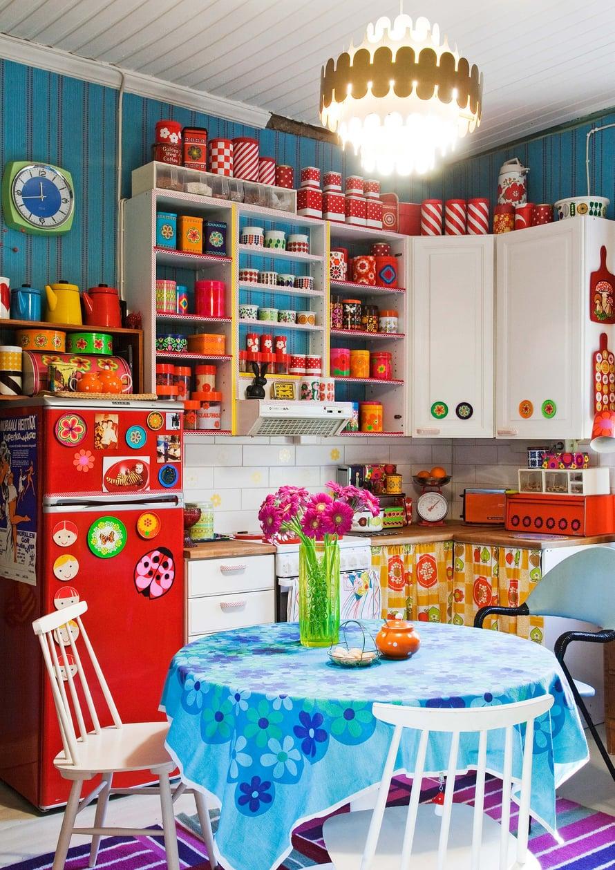 Keittiö on kuin pieni putiikki. Hyllyiltä voi bongata Esteri Tomulan suunnittelemia kattiloita, monille lapsuudesta tuttuja emalimukeja ja Fazerin karkki- tai kaakaopurkin. Kevytrakenteinen nojatuoli on kirpputorilta.