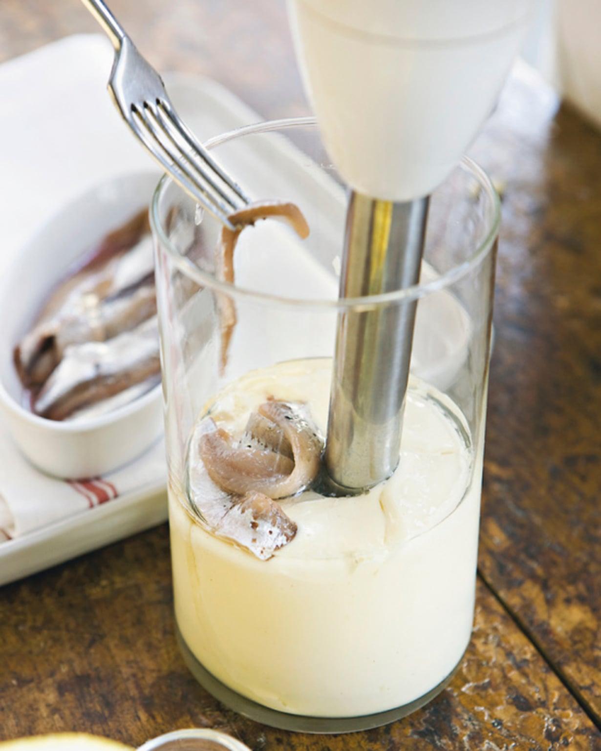 Kun majoneesi on muodostunut, lisää valkosipulinkynsi, anjovisfileet ja sitruunamehu. Sekoita tasaiseksi.