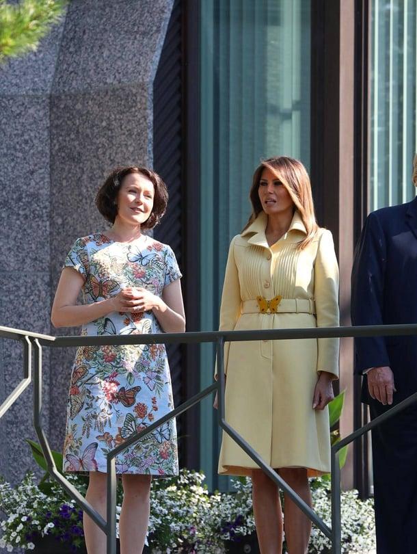 Presidenttien puolisot Jenni Haukio ja Melania Trump Mäntyniemen parvekkeella. Andiata tiedotti ylpeänä, että Jennin asu oli heidän mallistostaan. Helsingin Sanomien mukaan virkasiskon asu oli puolestaan Guccin, perhonen vyön solkena.