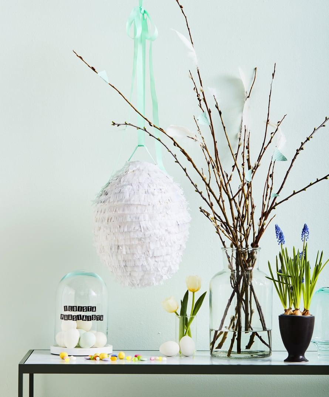 Liimaa pajunvitsoihin sulkia ja paperilippuja, jotka sopivat sävyiltään yhteen pinjatan kanssa. Tarrakirjaimet toivottavat hyvää pääsiäistä. Juhlan jälkeen ne on helppo nappaista pois.
