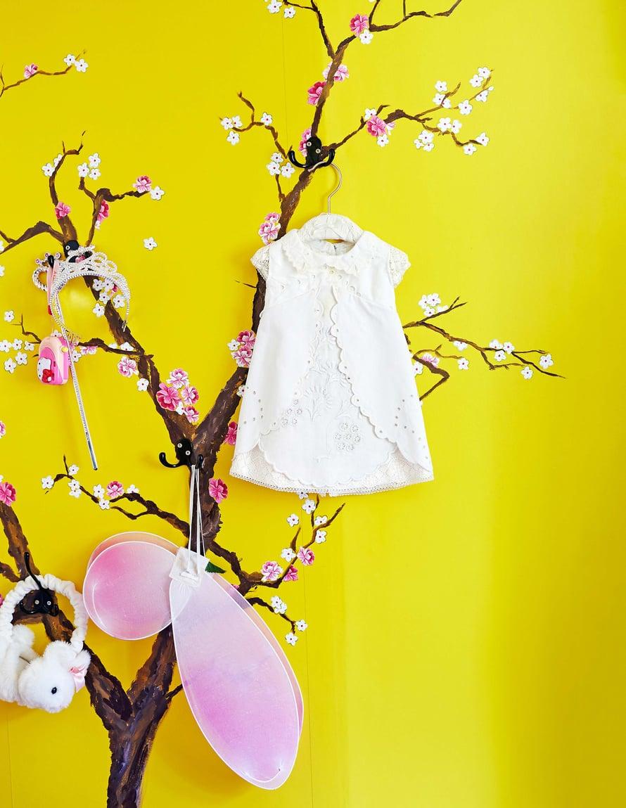 Lastenhuoneen sisustuksen idea lähti kirsikankukista. Oksan Helena maalasi seinälle itse, kukat on leikattu Eijffingerin tapetista.