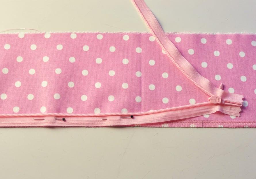 Asettele ja neulaa vetoketju paikoilleen oikeat puolet vastakkain, jolloin lukko on kangasta vasten. Vetoketjun ura asettuu kappaleen reunaan ja nauhaosa saumanvaraan.