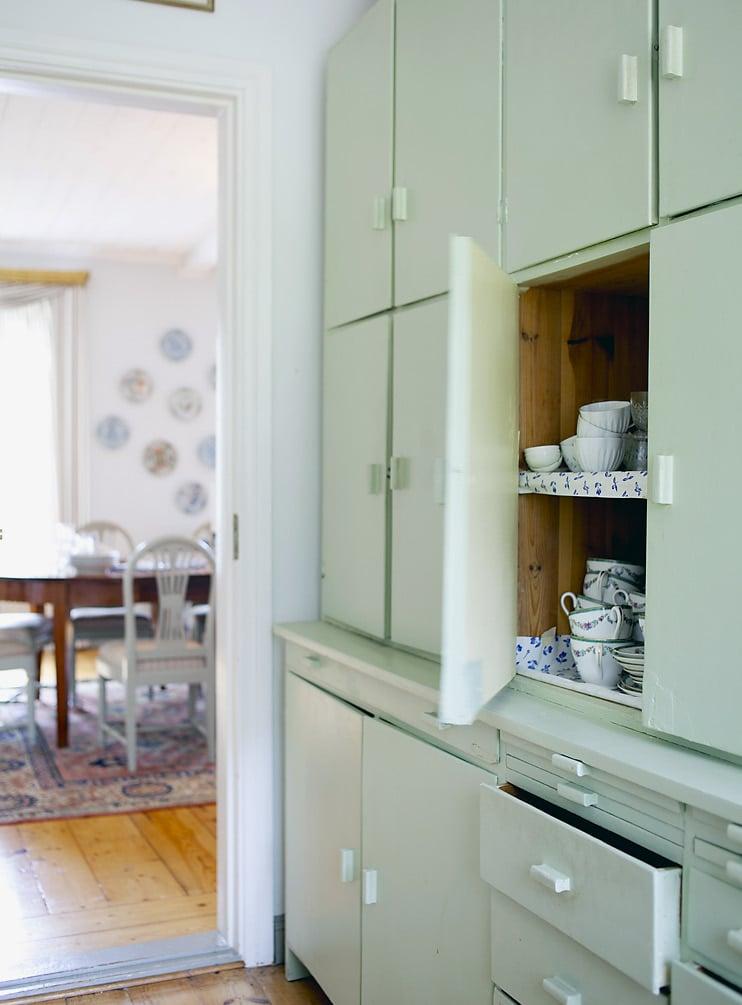 Mintunvihreät kaapit keittiön ja ruokasalin välisessä käytävässä ovat täynnä sinistä ja valkoista posliinia.